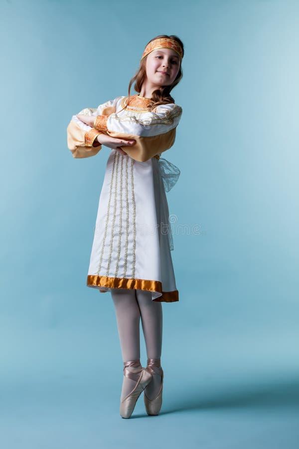 Gullig liten ballerina som poserar i folkklänning royaltyfri bild