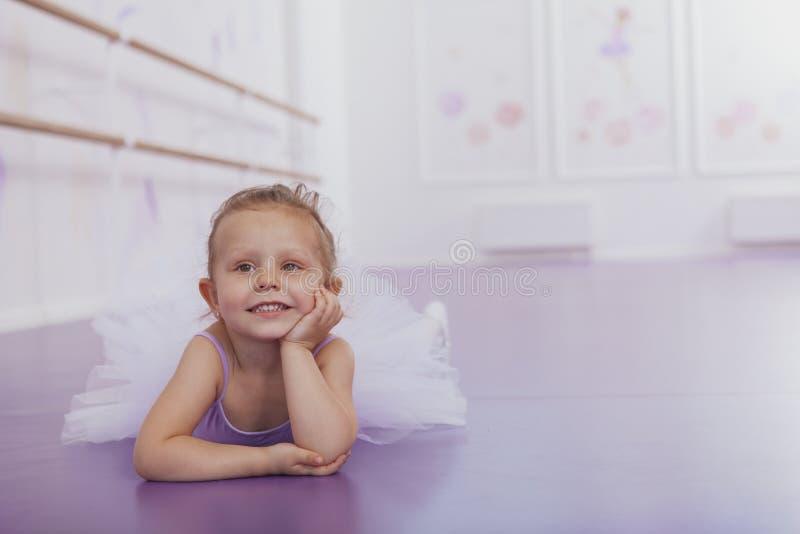 Gullig liten ballerinaflicka som övar på dansskola arkivfoton