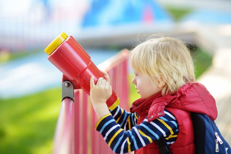 Gullig liten blond caucasian pojke, unge eller barn som utomhus ser till och med kikare på lekplats royaltyfri fotografi