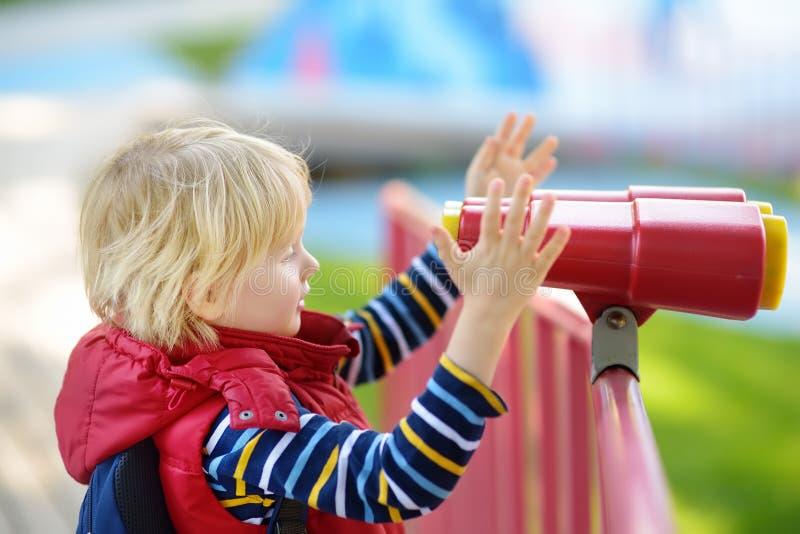 Gullig liten blond caucasian pojke, unge eller barn som utomhus ser till och med kikare på lekplats royaltyfria foton