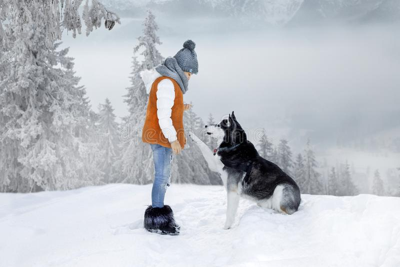Gullig liten blond flicka som spelar i snön med en skrovlig hund arkivfoto