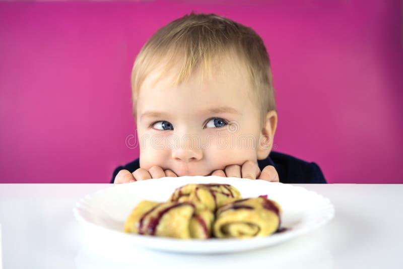 Gullig liten caucasian barnpojke som döljer bak tabellen och ser över tabellkanten på en platta av mat, en söt efterrätt på l royaltyfri bild