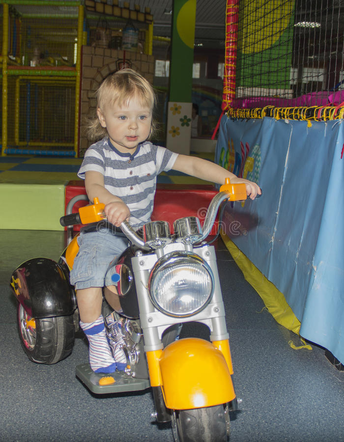 Gullig liten cyklist på vägen med motorcykeln arkivbilder