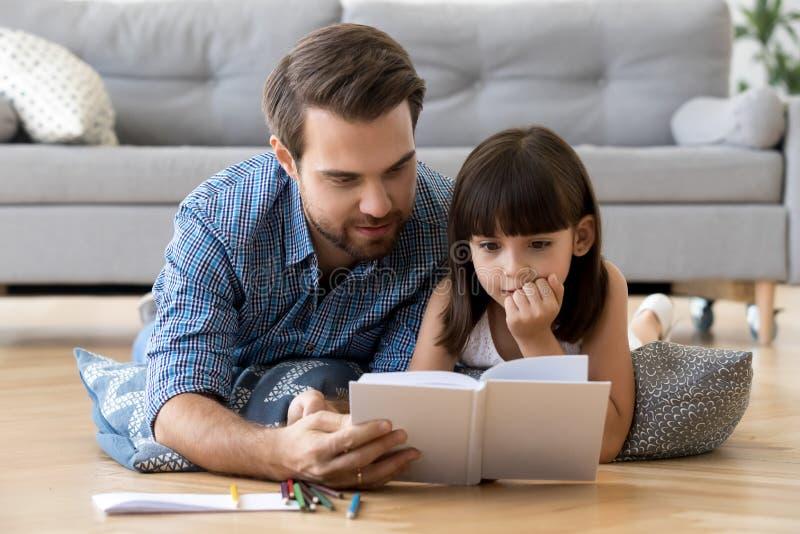 Gullig liten dotter som hemma lyssnar till farsaläseboken arkivfoton