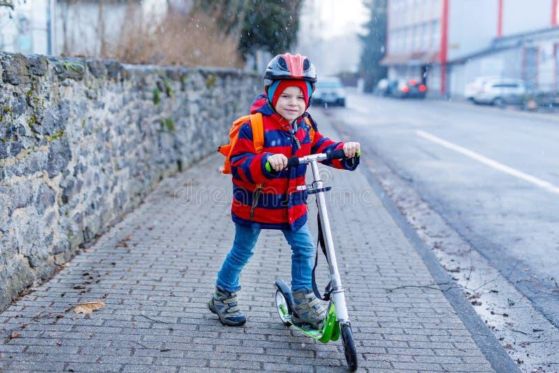 Gullig liten förskole- ungepojkeridning på sparkcykelridning till skolan barnaktiviteter som är utomhus- i vintern, vår eller arkivfoton