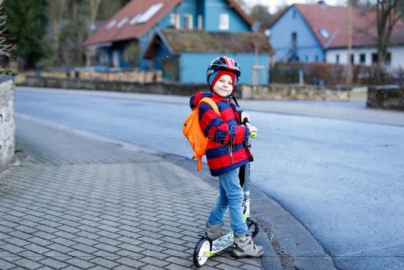 Gullig liten förskole- ungepojkeridning på sparkcykelridning till skolan barnaktiviteter som är utomhus- i vintern, vår eller arkivbilder