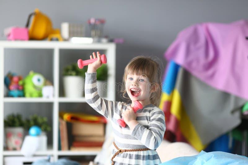 Gullig liten flicka att göra fysiska övningar hemma royaltyfri foto