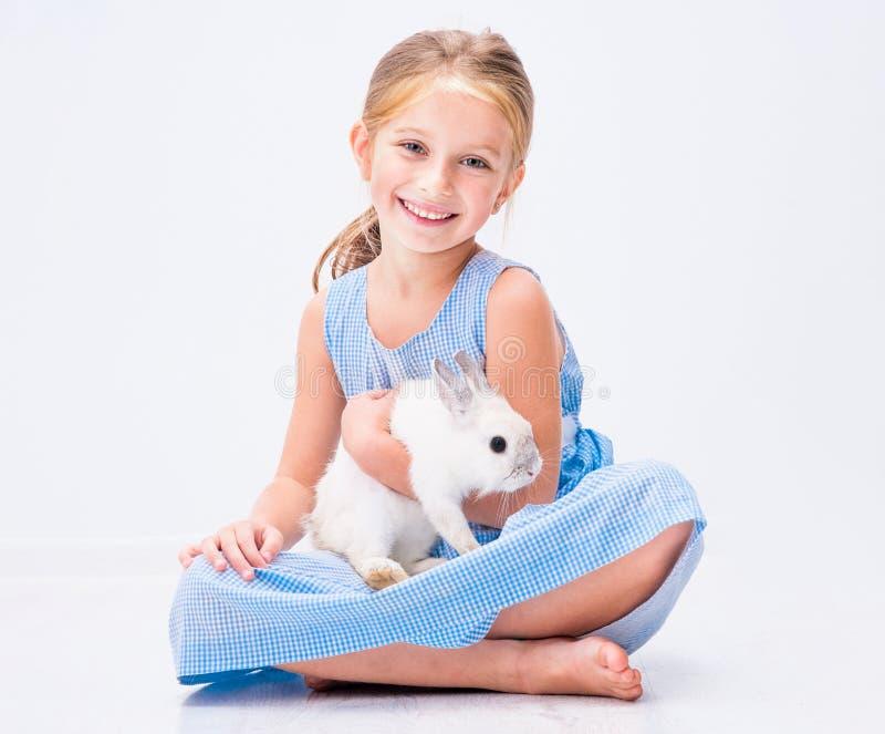 Gullig liten flicka en vit kanin royaltyfria bilder