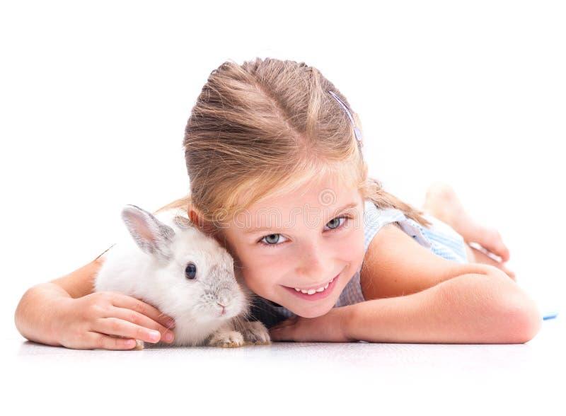 Gullig liten flicka en vit kanin royaltyfri foto