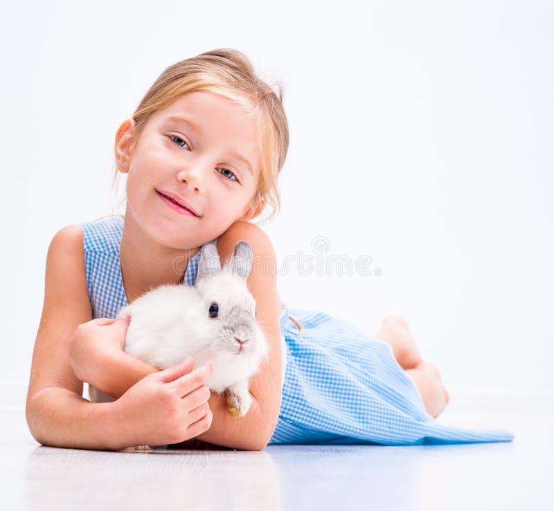 Gullig liten flicka en vit kanin arkivfoton