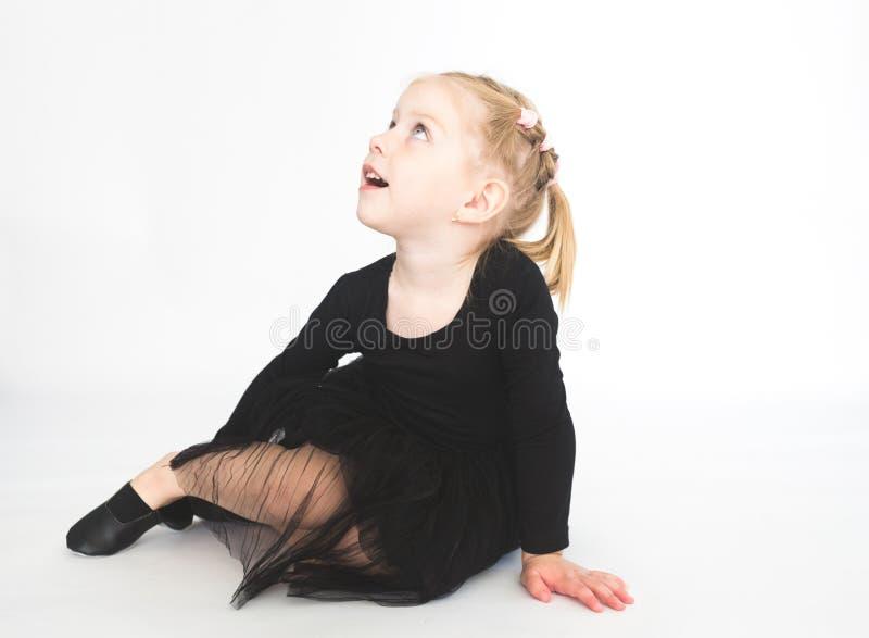 Gullig liten flicka i den h?rliga svarta kl?nningen som sitter p? golvet p? vit bakgrund arkivbild