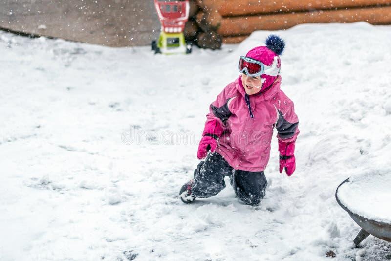 Gullig liten flicka i den rosa sportdräkten som har gyckel som utomhus spelar under snöfall i vinter Barn övervintrar säsongsbeto fotografering för bildbyråer