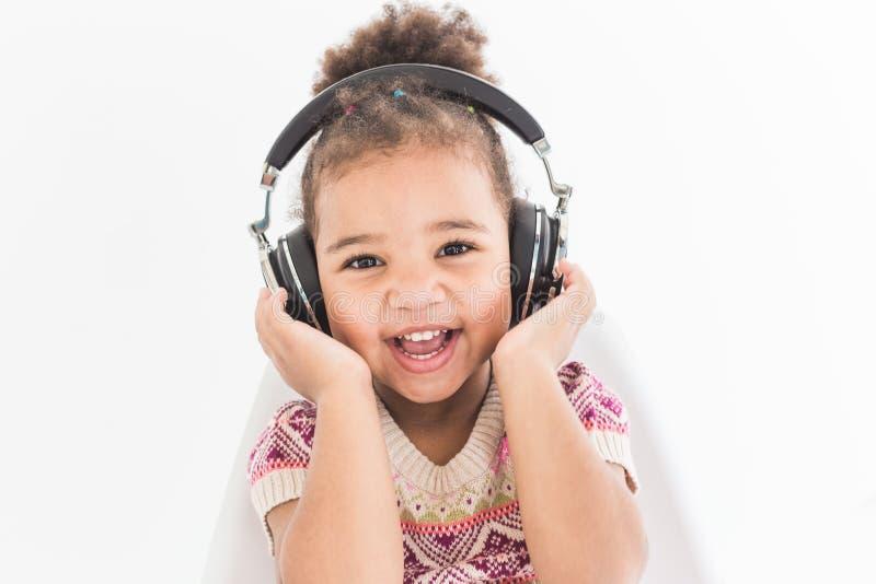 Gullig liten flicka i en färgrik klänning som lyssnar till musik med hörlurar på en vit bakgrund arkivfoton