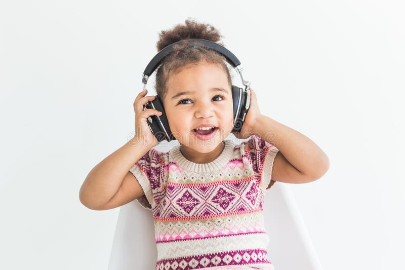 Gullig liten flicka i en färgrik klänning som lyssnar till musik med hörlurar på en vit bakgrund arkivfoto