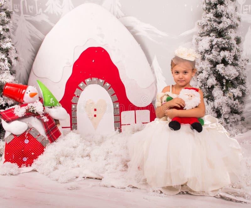 Gullig liten flicka i en vit trevlig klänning med en leksak av jultomten royaltyfri fotografi
