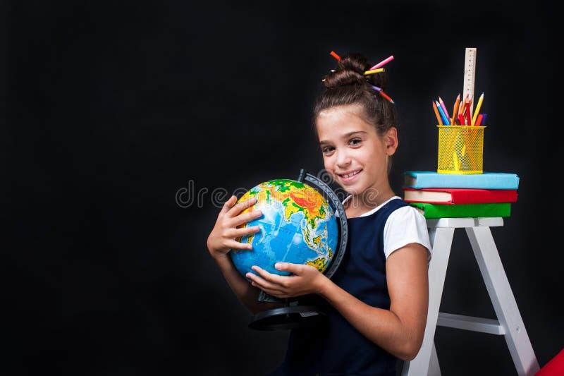 Gullig liten flicka i enhetlig kläder som går att skola placera text royaltyfria bilder
