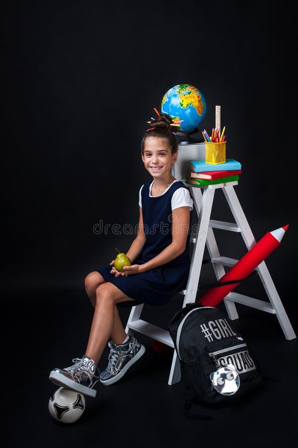 Gullig liten flicka i enhetlig kläder som går att skola placera text royaltyfria foton