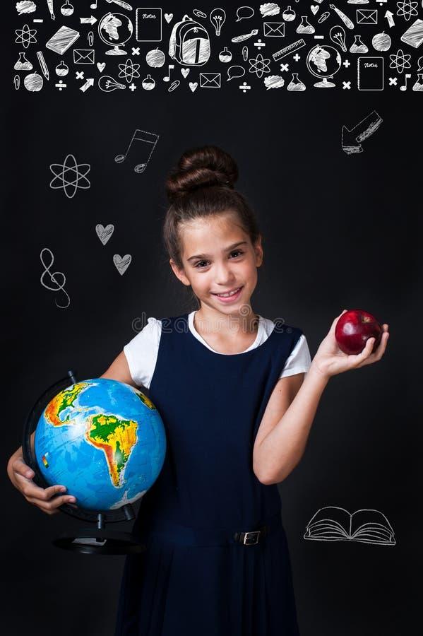 Gullig liten flicka i enhetlig kläder som går att skola placera text arkivbild