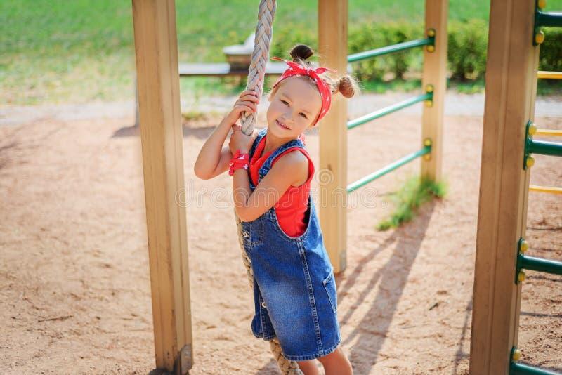 Gullig liten flicka i grov bomullstvilloveraller som klättrar en spänd lina i barns lekplats arkivbilder