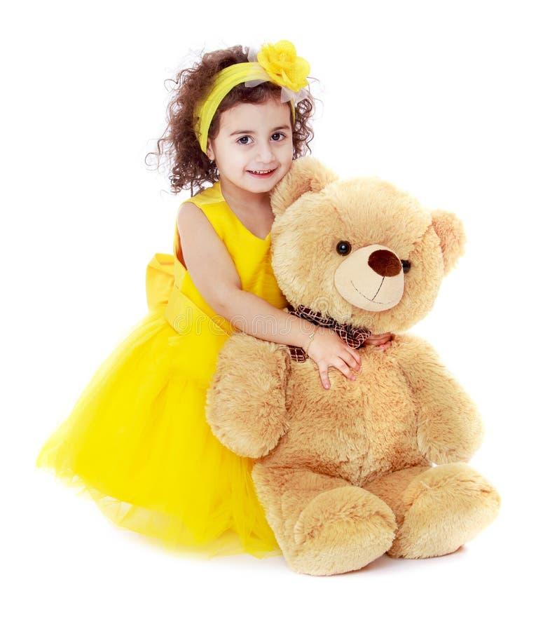 Gullig liten flicka i gult krama för klänning som är stort arkivbild