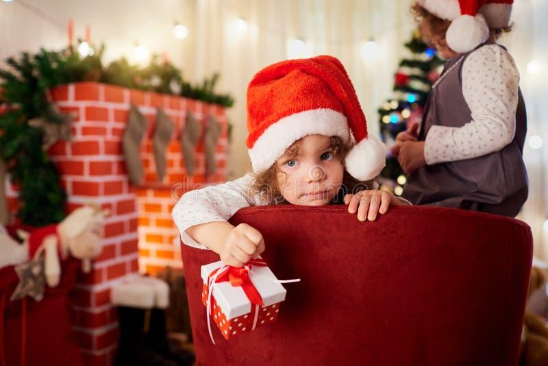 Gullig liten flicka i hatten av Santa Claus med en gåva i hand l arkivfoto