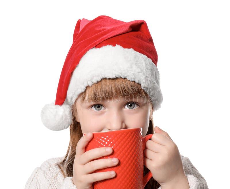 Gullig liten flicka i jultomtenhatt och med koppen av den varma kakaodrinken på vit bakgrund royaltyfri foto
