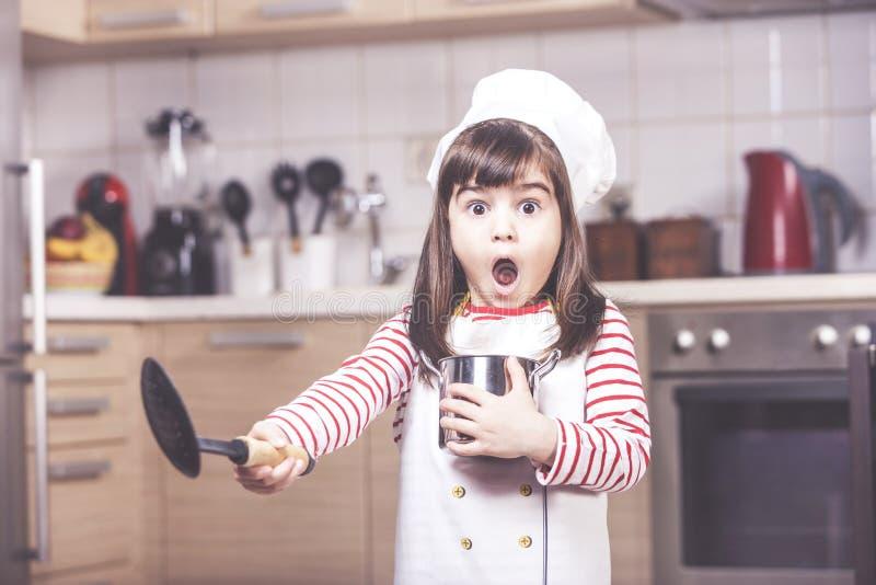 Gullig liten flicka i köket arkivfoto