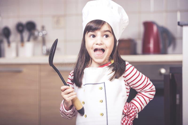 Gullig liten flicka i köket royaltyfri fotografi