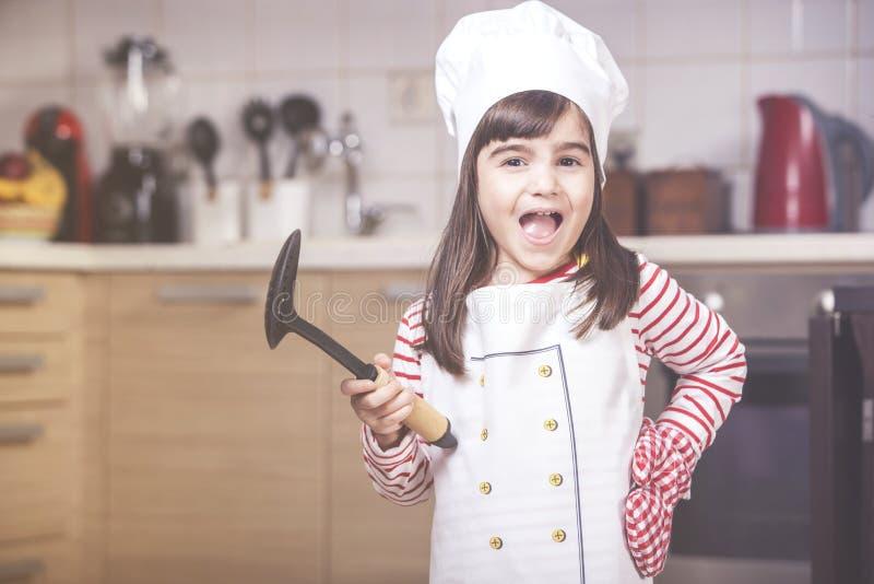 Gullig liten flicka i köket arkivbild