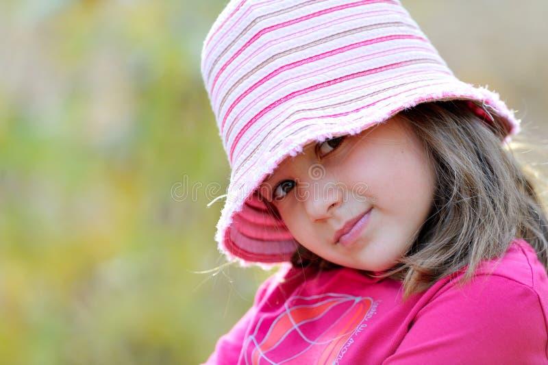 Gullig liten flicka i parkera i höst royaltyfria foton