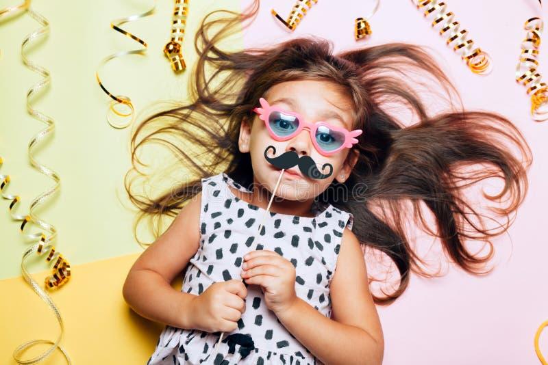Gullig liten flicka i roliga exponeringsglas med den pappers- mustaschen arkivbild