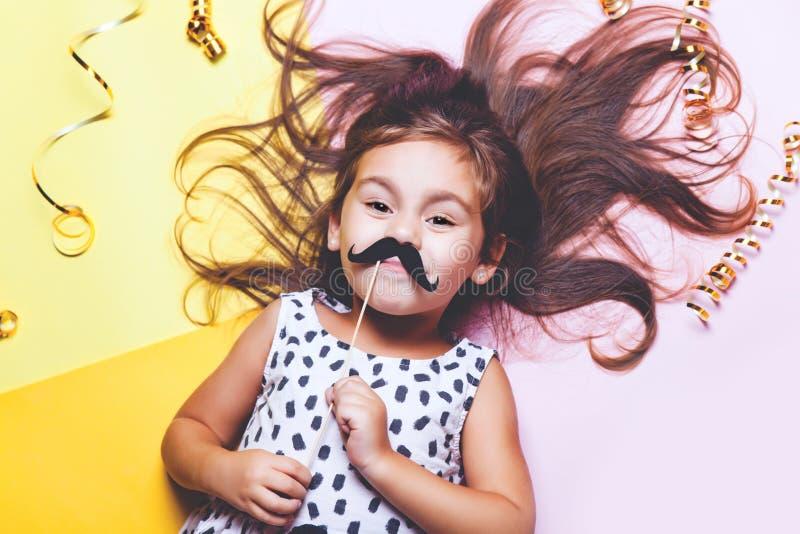 Gullig liten flicka i roliga exponeringsglas med den pappers- mustaschen royaltyfria foton