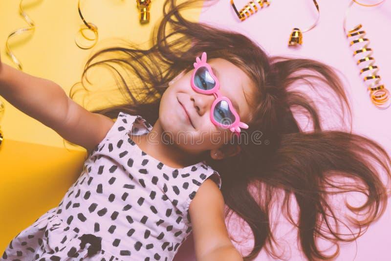 Gullig liten flicka i roliga exponeringsglas med plast- maskeradkanter på pinnen royaltyfri foto
