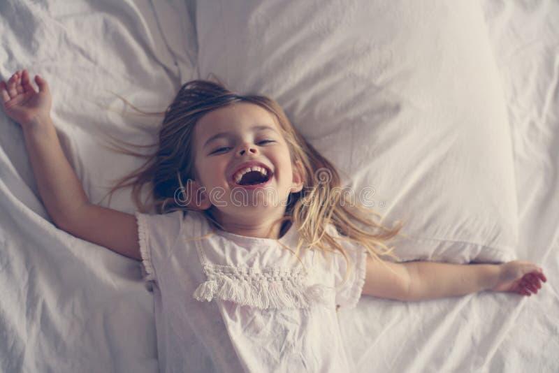 Gullig liten flicka i säng fotografering för bildbyråer