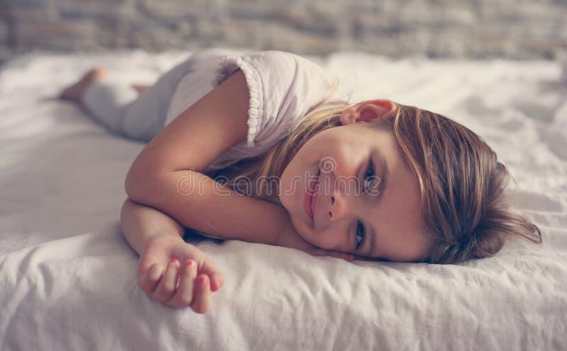Gullig liten flicka i säng royaltyfria foton