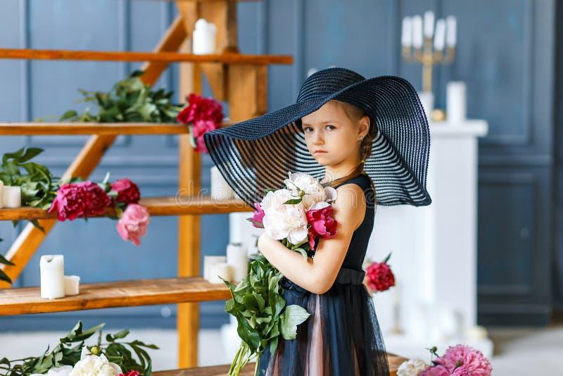 Gullig liten flicka i stor svart hatt med pioner i studio royaltyfria foton