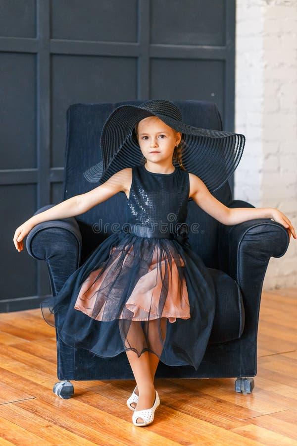Gullig liten flicka i stor svart hatt med pioner i studio royaltyfria bilder