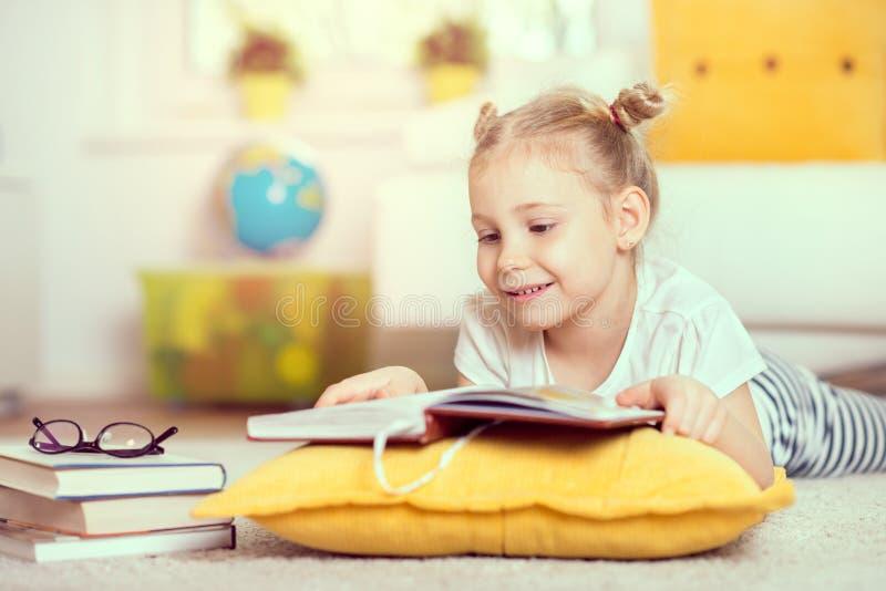 Gullig liten flicka läst bok hemma royaltyfri fotografi