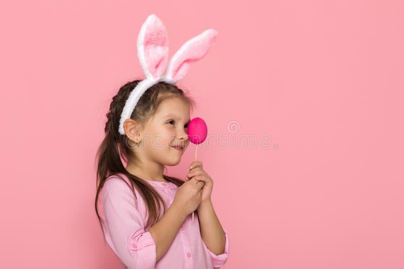Gullig liten flicka med öron för påskkanin som rymmer färgrika ägg royaltyfri bild