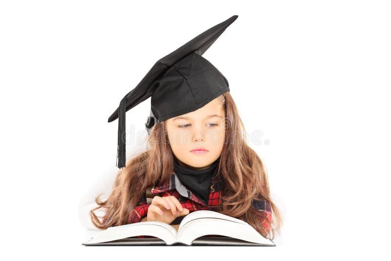 Gullig liten flicka med avläggande av examenhatten som läser en bok arkivfoton