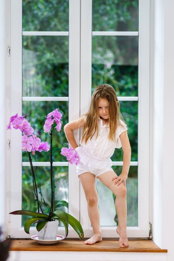 Gullig liten flicka med blommasammanträde på fönsterbräda av nya pvc-wi fotografering för bildbyråer