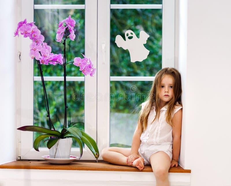 Gullig liten flicka med blommasammanträde på fönsterbräda av nya pvc-wi royaltyfri bild