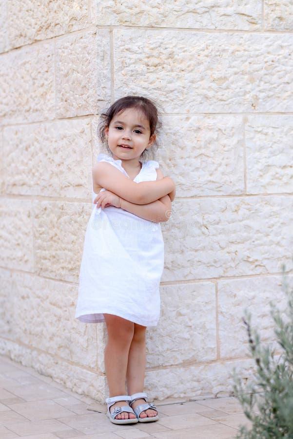 Gullig liten flicka med den utomhus- vita klänningen bl?a pojkeskrivbordflickor ser sittande surfa f?r havet arkivbilder