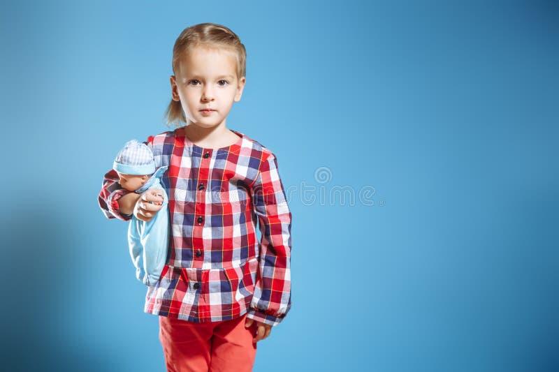 Gullig liten flicka med dockan på blå bakgrund fotografering för bildbyråer
