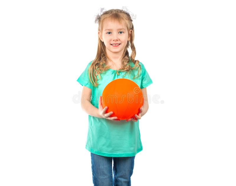 Gullig liten flicka med en boll som ser in i kameran och le royaltyfria bilder