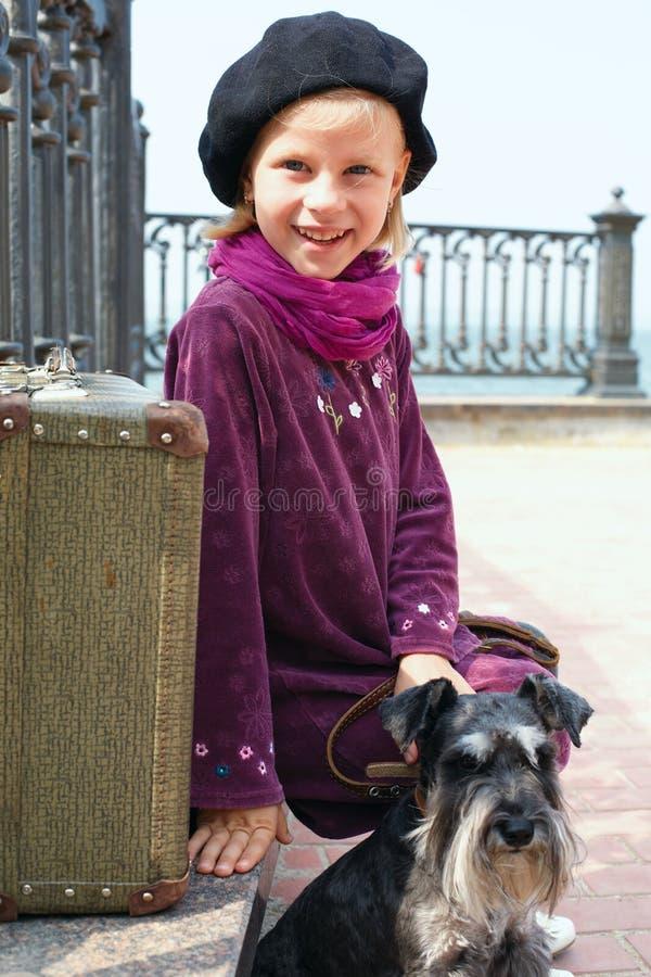 Gullig liten flicka med en hund och en resväska royaltyfri fotografi