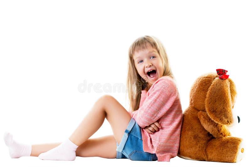 Gullig liten flicka med en stor nallebjörn som sitter på golvet arkivfoto