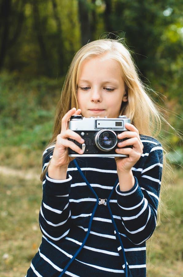 Gullig liten flicka med en tappningrangefinderkamera royaltyfri foto