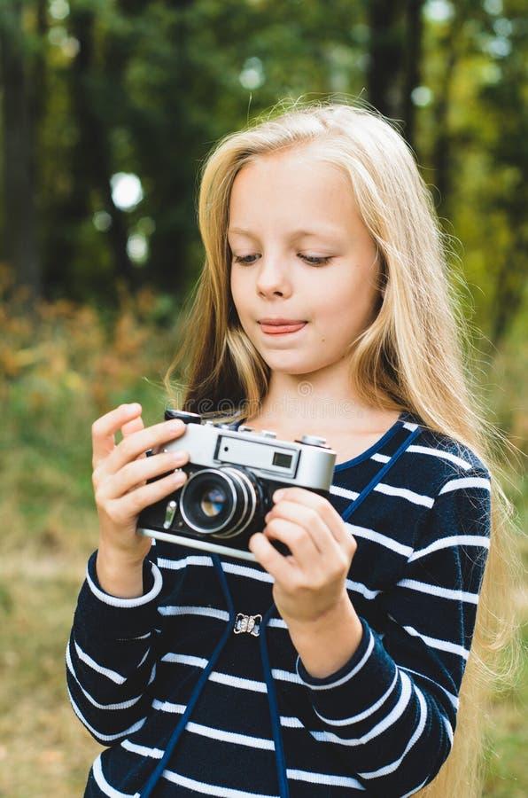 Gullig liten flicka med en tappningrangefinderkamera arkivbilder