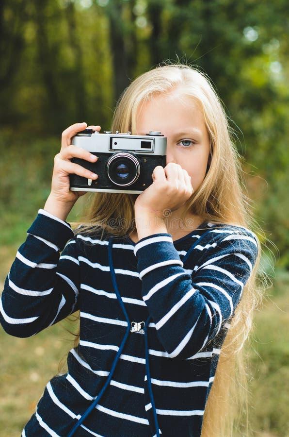 Gullig liten flicka med en tappningrangefinderkamera royaltyfria bilder